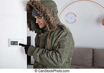 Man In Warm Clothing Pointing To Current Room Temperature -...