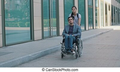 Young man in wheelchair and woman at the city