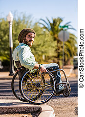 Young Man in Wheelchair at City Curb