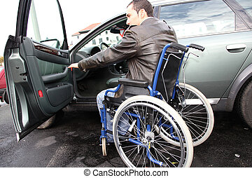 Young man in wheelchair getting in his car