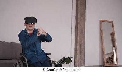 Young man in wheelchair playing at video games in home -...
