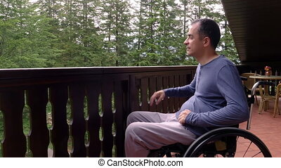 Young man in wheelchair relaxing on terrace - Smiling young...