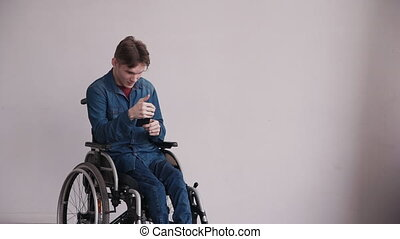 Young man in wheelchair using his smartphone at home - Young...