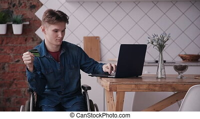 Young man in wheelchair using laptop and credit card - Young...