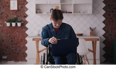 Young man in wheelchair using laptop pc at home - Young and...