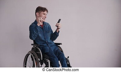 Young man in wheelchair using modern smartphone at home