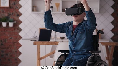 Young man in wheelchair using virtual reality helmet at home...