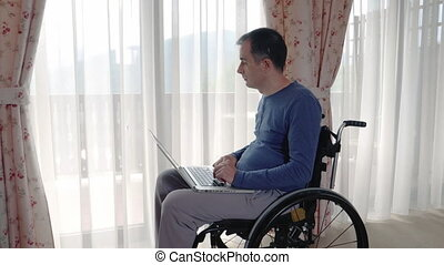 Young man in wheelchair working at laptop computer at home...
