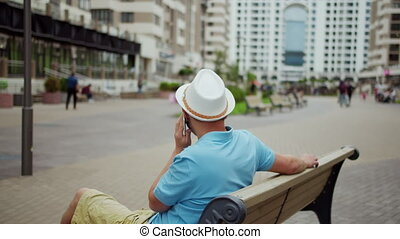 Young man in white hat talking on the phone while sitting on a bench, camera movement