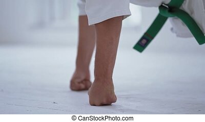 Martial Art Master In White Kimono Doing Push Ups In Gym. White Floor. Selective Focus On Strong Hands.