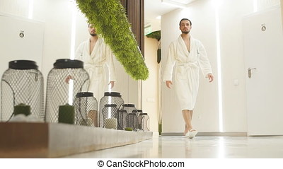 Young man in white robe walks down the hall of luxurious Spa...