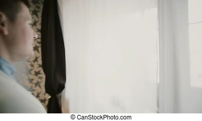 Young man in white suit approaches a window. Groom preparing for a wedding day. Morning before ceremony.