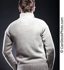 Young man in white sweater rear view
