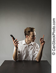 Young man in white using smartphone.