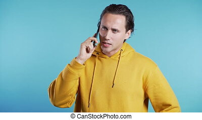 Young man in yellow wear talking on mobile phone on blue background. Trendy guy have conversation. Smartphone, technology concept