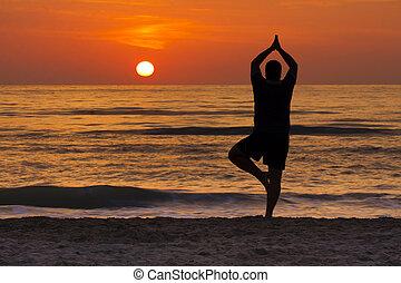 Young man in yoga pose tree meditating at dawn at sea