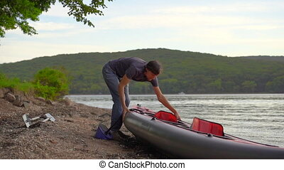 Young man inflates his kayak and prepares it for paddling in...