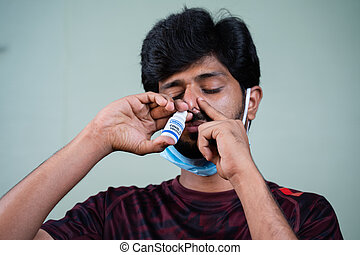 Young Man inhaling Coronavirus covid-19 nasal Vaccine spray to nostril to protect fron viral infection