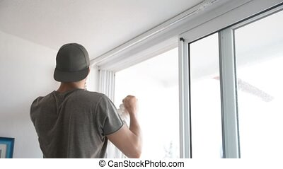 Young man installing curtains over window - Young handsome...