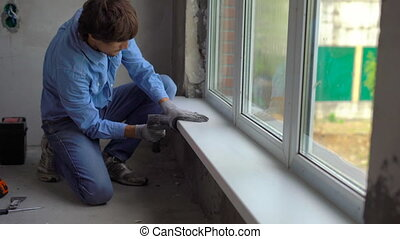 Young man installing windowsills of a plastic window.