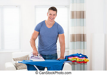 Young Man Ironing Clothes