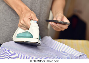 young man ironing clothes while using a smartphone