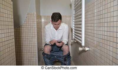 Man holds his smartphone to pass the time sitting on toilet bowl in lavatory. He is reading morning news browsing mobile phone before work.