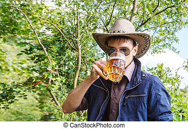 young man is drinking beer in the park