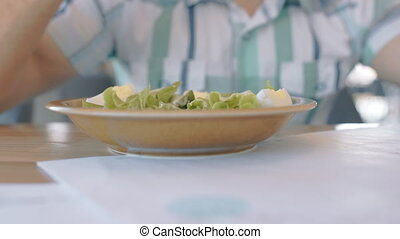 Young man is eating salad sitting at table in cafe.