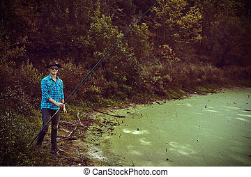 man is fishing - Young man is fishing on the lake on a warm ...