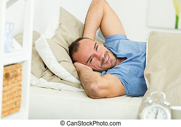 young man is happy to sleep in his warm bed
