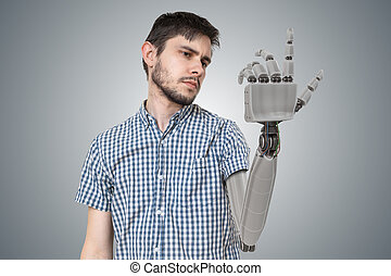 Young man is looking at his prosthetic robotic hand. 3D rendered