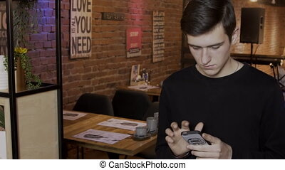 Young man is looking at phone screen while standing in cafe.