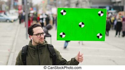 Young man is looking at poster with green screen in his hand...