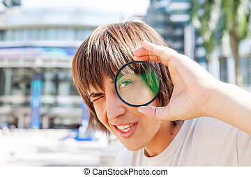 Young man is looking through the lens filter. Transparent glass device for camera. Sunny day in town.