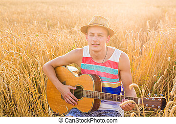 Young man is playing guitar in the field