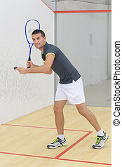 young man is playing indoor tennis