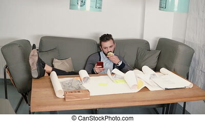 young man is resting avoiding the work sitting on sofa uses smartphone and eating apple put his feet on the table