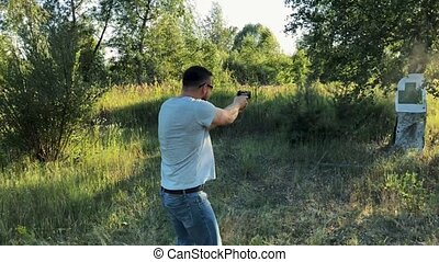 Young man is shooting from a gun at the target, close up. Slow motion