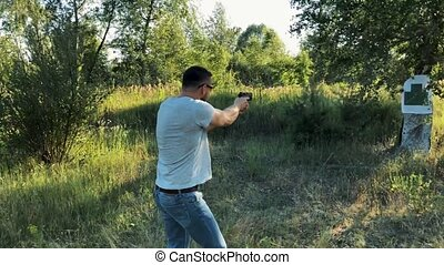 Young man is shooting from a gun at the target, close up