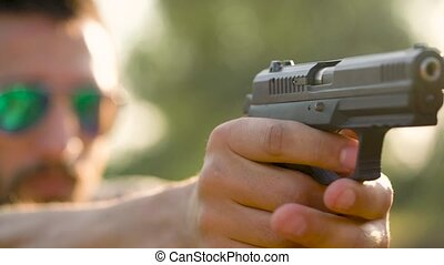 Young man is shooting from a gun, close up. Slow motion