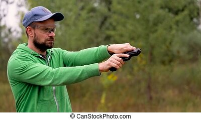 Young man is shooting from a gun, close up