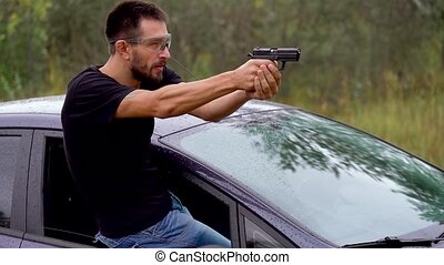 Young man is shooting from a gun leaning out the window of...