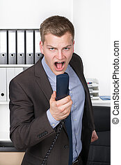 Young man is shouting into the phone
