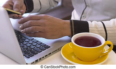 Young man is sitting at table with laptop in cafe.