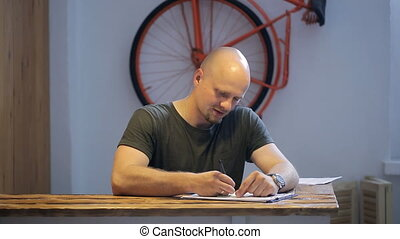 Young man is sitting in studio making notes.