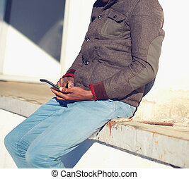 Young man is sitting with a smartphone in the city