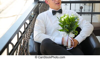 Young man is sitting with wedding bouquet on the balcony