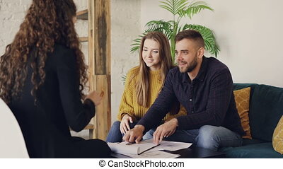 Young man is talking to housing agent, signing document and taking house key, clasping hands with realtor then kissing his wife. Buying real estate and people concept.