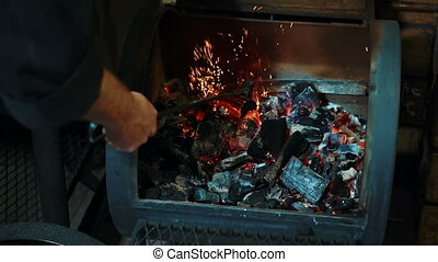 Young man is turning coals in smokehouse oven indoors....